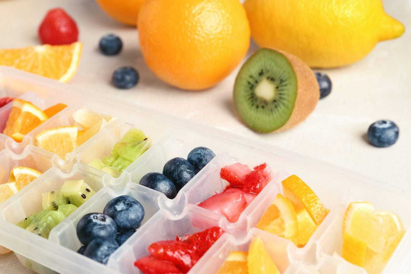 Ice cube tray with different fruits and berries on table